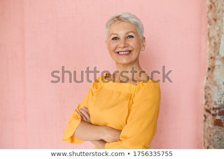 Portrait of a smiling brunette businesswoman posing with the arms crossed against a white background stock photo © wavebreak_media