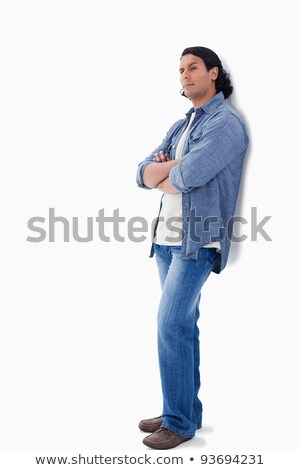 Man raising his eyebrow and leaning against a wall with white background Stock photo © wavebreak_media