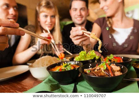 Young people eating food in Thai restaurant Stock photo © Kzenon