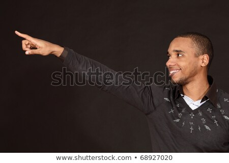 Young african-american man points to smth Stock photo © deandrobot