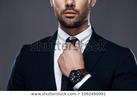 handsome businessman straightening his tie stock photo © deandrobot