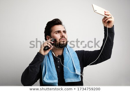young man using his smartphone in the bathroom Stock photo © nito