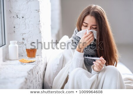 Stock photo: The hand of young sick woman with thermometer