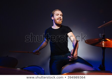 Brutal excited young man drummer with beard playing drums  Stock photo © deandrobot