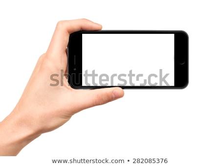 Hand holding mobile smartphone with blank screen horizontally on white background Stock photo © Customdesigner