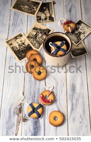 cookies decorated like lifebuoys, one floats in a cup. Vintage image stock photo © faustalavagna