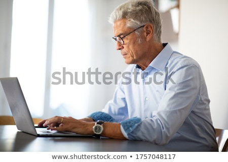 closeup portrait elderly man sitting at table working on laptop computer stock photo © ichiosea