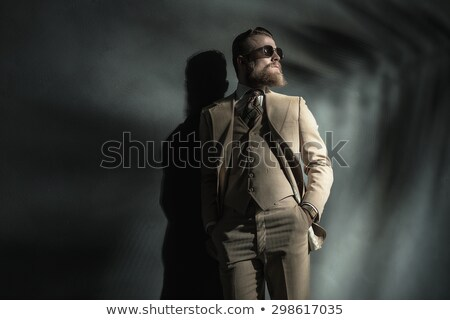 portrait of a gentleman leaning against grey wall  Stock photo © feedough