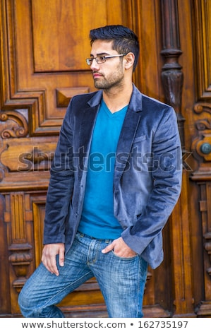 sad man wearing jeans jacket standing with hands in pockets stock photo © feedough