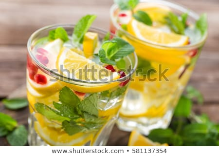 Lemon mojito cocktail with fresh mint and pomegranate, cold refreshing summer drink or beverage with Stock photo © yelenayemchuk