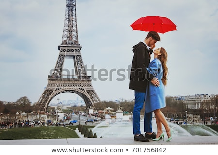 Man in love about to kiss beautiful woman under umbrella, romantic date in Paris stock photo © motortion