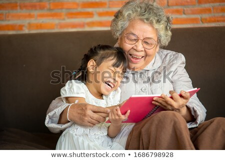 Woman and granddaughter reading together Stock photo © IS2