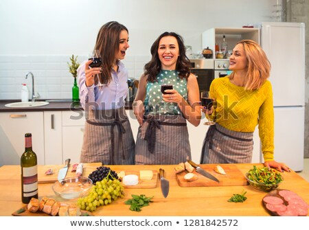 female friends preparing a meal together and drinking red wine i stock photo © dashapetrenko