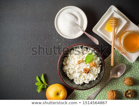 glass of milk and bowl of cottage cheese on white stone kitchen table backgroundspace for text stock photo © denismart