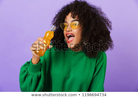 African woman isolated over violet background drinking soda. Stock photo © deandrobot