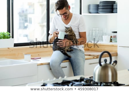 Portrait of handsome young man playing with cat and drinks coffee stock photo © galitskaya