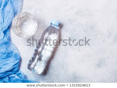 Bottle of sparkling mineral water with glass of ice and blue cloth on white Stock photo © DenisMArt