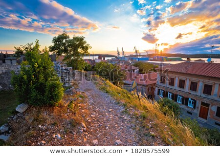 Town of Pula coastline and shipyard cranes sunset view Stock photo © xbrchx