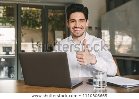 Image of businesslike man wearing white shirt sitting on table i Stock photo © deandrobot