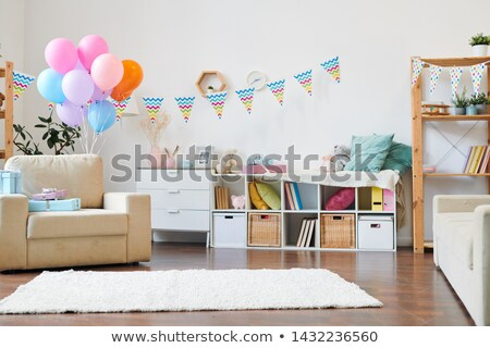 Bunch of colorful balloons and stack of giftboxes on armchair in the living-room Stock photo © pressmaster