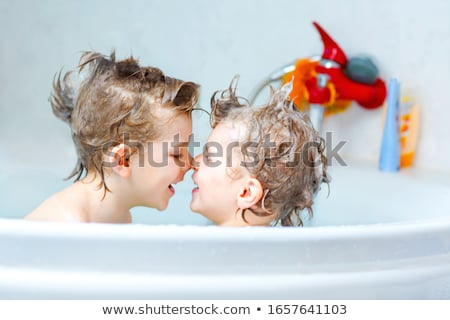 Two little boys having fun with water by taking bath in bathtub Stock photo © Lopolo