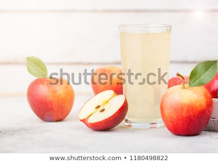 Glass of fresh organic apple juice with braeburn pink lady apples in box on wooden background Stock photo © DenisMArt