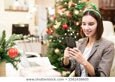 Pretty young smiling businesswoman in xmas headband making selfie by workplace Stock photo © pressmaster