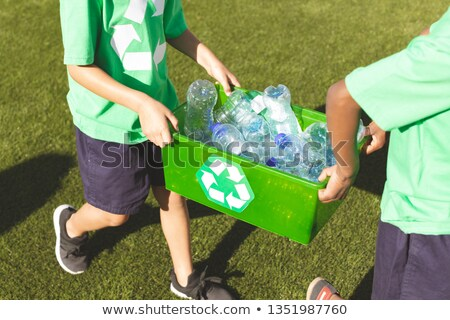 Low section of nulti ethnic schoolboy walking and holding tray with plastic bottles in playground  Stock photo © wavebreak_media