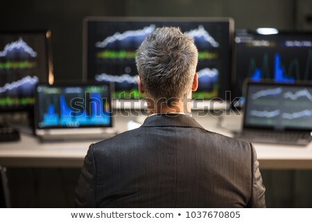 Stock Market Broker Looking At Graphs On Laptop Stock photo © AndreyPopov