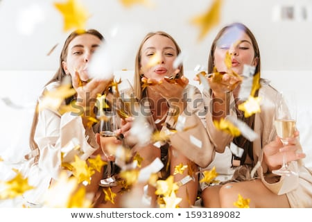 Three cheerful girls friends wearing dressing gowns sitting on bed Stock photo © deandrobot