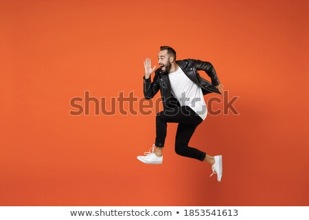 Image of young bearded man wearing basic white t-shirt running Stock photo © deandrobot