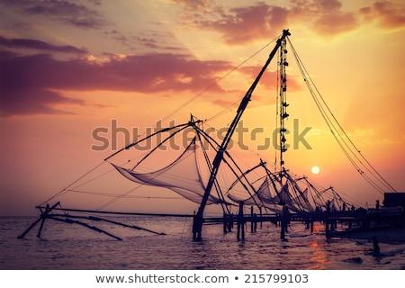 Fisherman and chinese fishnets on sunset. Kochi, Kerala, India Stock photo © dmitry_rukhlenko