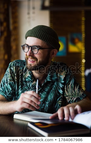 Businessman sitting indoors and writing plan in his diary stock photo © HASLOO