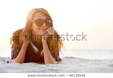 Foto stock: Red Head Girl With Headphones At The Beach In Sunrise