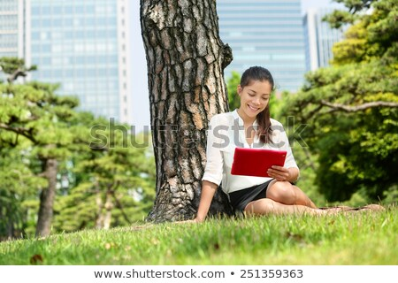 happy young woman reading ebook near books stock photo © Rob_Stark