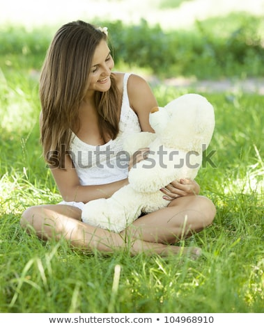 beautiful teen girl with teddy bear in the park at green grass stock photo © massonforstock