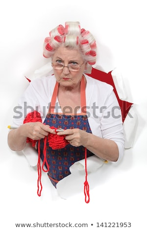 Stock photo: Granny with her hair in rollers and knitting