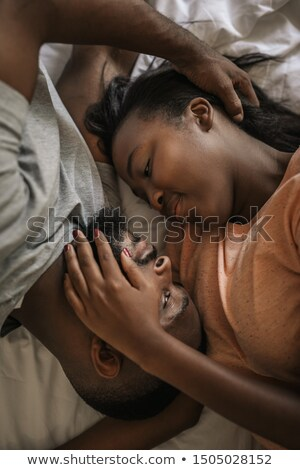 close up of a couple lying on a bed hugging while looking at each other stock photo © wavebreak_media