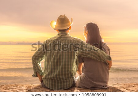 casual man with hand on hat and the sunset behind Stock photo © feedough