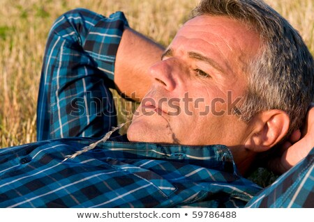 casual man outdoor with straw in mouth looks away stock photo © feedough