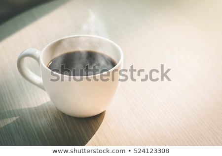 Coffee cup on a white wood table with cake in the background Stock photo © phila54