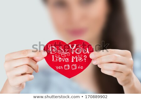 woman holding red heart with question do you love me stock photo © hasloo