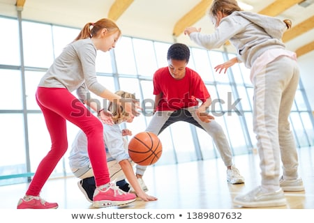 elementary school pupils playing basketball in gym stock photo © highwaystarz