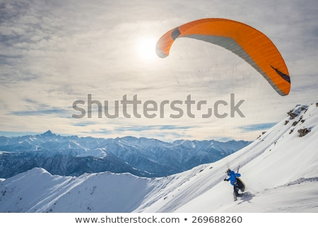 paraglider in snowy winter mountains at sun day stock photo © bsani