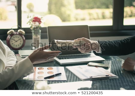 Close-up of businessman's hand giving bills of dollars Stock photo © deandrobot