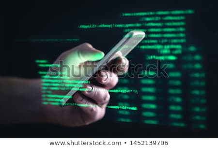 Thief using a stolen mobile phone Stock photo © AndreyPopov
