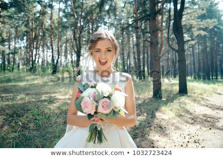beautiful smiling bride with wedding bouquet of flowers at park stock photo © victoria_andreas