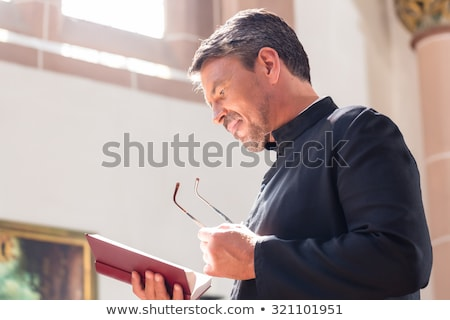 Catholic priest reading bible in church Stock photo © Kzenon