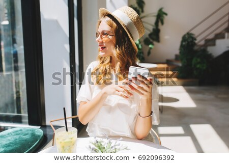 Pretty blonde girl holding hat in a cafe Stock photo © deandrobot
