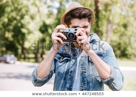 Handsome young hipster guy holding retro camera wearing hat Stock photo © deandrobot